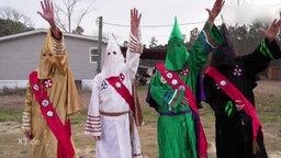 Mitglieder des Ku-Klux Klans heben die Hand.