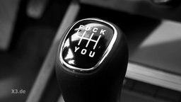 Fuck you stehtauf dem Schalthebel eines Autos.