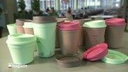 viele Mehrwegkaffeebecher auf einem Tisch