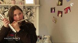 Tochter, die auf der Flöte spielt.