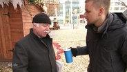 Tobias Schlegl, mit Spendendose, redet mir einem älteren Herren