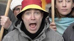 Ein Mann, mit aufgerissenem Mund, trägt einen Deutschland-Hut