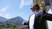 Motivationstrainer Jürgen Höller streckt beide Arme aus.