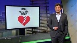 """Christian Ehring moderiert extra 3, auf dem Bildschirm im Hintergrund steht """"Ein Herz für Merz"""""""