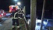 Die Feuerwehr sichert ein leckgeschlagenes Schiff.