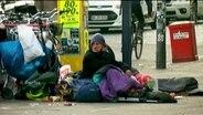 Ein Obdachloser sitzt auf der Straße.