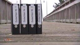 Auf einer Brücke wurden vier Ordner aufgestellt, mit den Titeln von Gutachten 1-4.