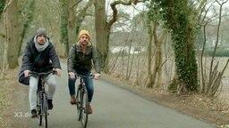 Zwei Perosnen fahren auf der Landstraße Fahrrad.