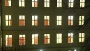 Ein Gebäude bei Dunkelheit und alle Räume sind beleuchtet.