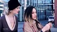 Eine Frau von 1919 steht verwirrt hinter einer Frau aus dem Jahre 2019 die ihre Smartphone in der Hand hält.