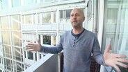 Ein Mann steht auf einem Balkon mit ausgebreiteten Armen