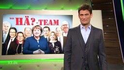 Christian Ehring im Studio, auf der Anzeigetafel ist das Hä-Team abgebildet.