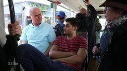 Ein älterer Mann sitzt neben einem dunkelhäutigen Mann im Bus.