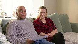 Ein Mann sitzt mit seiner Frau auf der Couch.