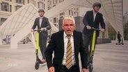 Heinz Strunk vor einem Bild mit zwei Anzugträgern auf E-Rollern.