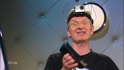 Ein Mann mit Kamera auf dem Kopf und wahnsinnigem Blick.