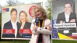 Eine Reporterin zwischen zwei Wahlplakaten.