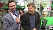 Ein Reporter von Extra 3 und Robert Habeck.