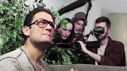 Christian Ehring mit Brille, daneben eine Zimmerpflanze, hinter der sich ein Kamerateam versteckt.