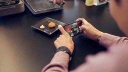 Auf einem Teller ist ein Hähnchen-Nugget aus Kunstfleisch angerichtet. Reporter Han Park fotografiert es mit seinem Smartphone.