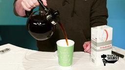 Kaffee wird in einen Becher gegossen.
