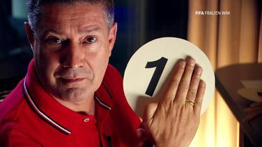 Ein Mann hält ein Schild hoch, auf dem eine Eins zu sehen ist. Eine andere Zahl hält er mit der Hand verdeckt.