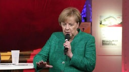 Kanzerlin Merkel am Mikrofon.