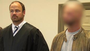 Ein Angeklagter steht neben seinem Verteidiger. | Screenshot NDR