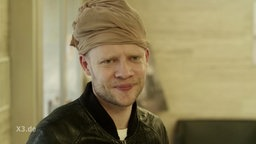 Ein Mann mit Strumpfhose auf dem Kopf begeht einen ökologisch korrekten Banküberfall.