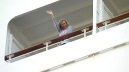 Eine Besucherin eines veganen Kreuzfahrtschiffs winkt von ihrem Balkon.