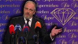 """Torsten Sträter steht vor einer Plakatwand mit der Aufschrift """"Die Superreichen"""", vor ihm 7 Mikrofone."""