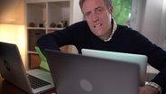 Ein Hasskommentator mit mehreren Laptops