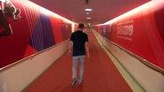 Frank Busemann schreitet einen roten Gang in einem Stadion entlang.