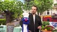 Grobi als Koch, mit einer Kochmütze und einer Schürze, mit Steffen Henssler.