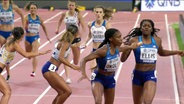 Stabwechsel bei den 4 x 400 Metern der Frauen in der Qualifikation während der Leichtathletik-WM 2019 in Doha: Die Amerikanerin Ellis gibt den Stab an ihre Kollegin Okolo weiter, im Hintergrund sieht man Läuferinnen aus Großbritannien und Belgien.