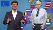 Der Moderator Christian Ehring vor einem Bild von Boris Johnson