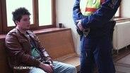 Rui Pinto sitzt in Handschellen auf einer Bank