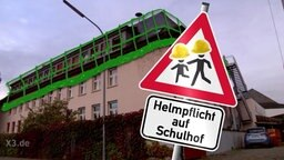 """Auf einem Schild einer Fotocollage steht: """"Helmpflicht auf dem Schulhof."""""""