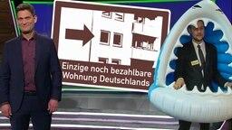 Tobi Schlegl und zwei Frauen einer Messe halten ein Schild, auf dem geschrieben steht: Ein Herz für Immobilienkonzerne.