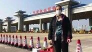 Une jeune femme avec un respirateur se tient dans une rue de Chine.
