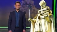 """Christian Ehring steht vor einem Bild, dass einigen Heiligen """"Bürokratius"""" zeigt."""