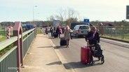 Touristen mit Rollkoffern auf der Strasse