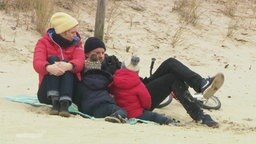 Eine Familie mit zwei kleinen Kindern sitzt zusammen am Strand. Sie alle tragen dicke Jacken, Mützen und Schals