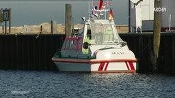 Ein Boot schwimmt auf dem Wasser, neben einem Anleger.
