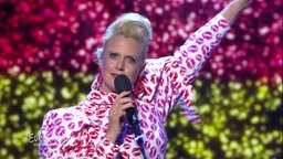 Barbara Schöneberger singt vor einer glitzernden Deutschlandflagge.