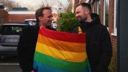 Schwules Pärchen mit Regenbogenflagge