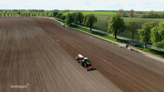 Widok ze szczytu dużego pola, po którym jedzie traktor.