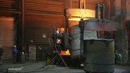 Eine Produktionshalle der Eisengießerei Torgelow, in einem riesigem Bottich glüht geschmolzenes Eisen.