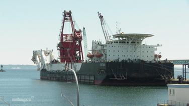 Ein großes Verlegeschiff für Pipelinerohre liegt an einer Pier.