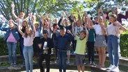 Schülerinnen und Schüler posieren für ein Klassenfoto.